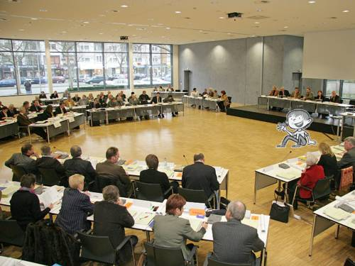 Mitglieder der Regionsversammlung sitzen auf Stühlen und an Tischen, die kreisförmig aufgestellt sind. Die Zeichnung einer sitzenden Person ist hinzugefügt.