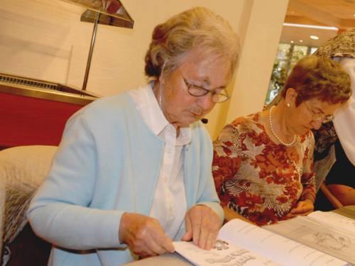 Zwei ältere Damen sitzen an einem Tisch und blättern in Unterlagen.