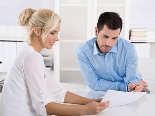 Eine Frau und ein Mann sitzen an einem Bürotisch und besprechen etwas. Die Frau hält Unterlagen in der Hand und zeigt sie dem Mann