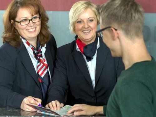 Zwei Frauen tragen Dienstkleidung mit einheitlichen Halstüchern und Blazern. Sie stehen hinter einer Infotheke und lächeln einen jungen Mann an. Alle drei Personen legen die Hand auf eine Broschüre, der Mann blickt auf die Broschüre.