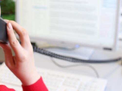 Eine Frau an einem Bildschirmarbeitsplatz, die gerade telefoniert.