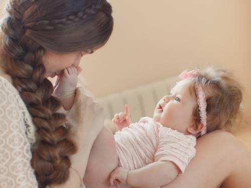 Ein Baby liegt rücklings auf den Beinen einer Frau, die Frau berührt mit der Nase die nackten Füße des Babys.