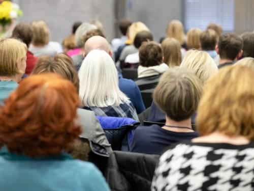 Frauen sitzen auf Stühlen und folgen dem Programm einer Veranstaltung.