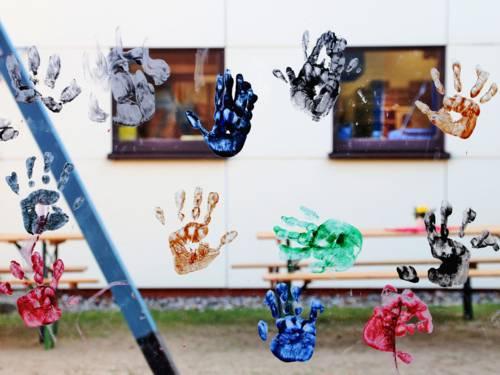 Handabdrücke in verschiedenen Farben auf einer Fensterscheibe