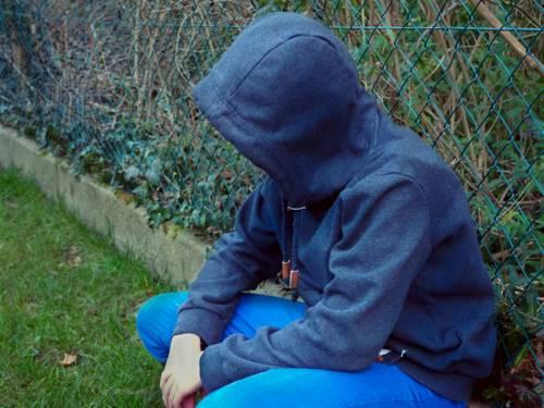 Ein Jugendlicher hockt vor einem Maschendrahtzaun.
