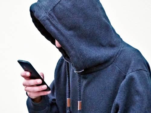 Ein Jugendlicher schaut mit hängenden Schultern in sein Smartphone.