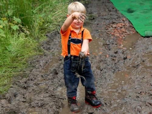 Ein kleiner, blonder Junge trägt eine Latzhose, ein orangefarbenes Polohemd und Schnürstiefel. Er streckt die Arme aus und lässt Matsch von der oberen Hand in die untere fallen. Er steht auf durchnässtem, matschigem Boden. Am Rand wächst hohes Gras.