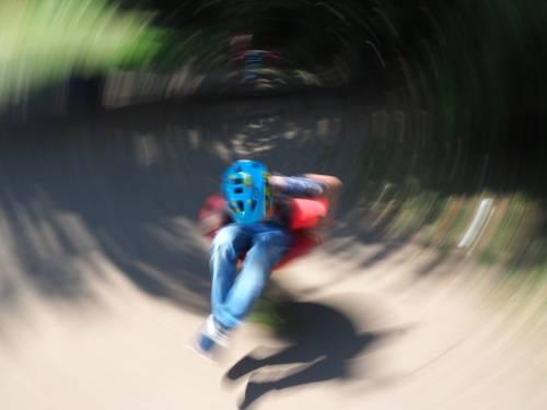 Ein Kind dreht sich mit hoher Geschwindigkeit auf einem Spielplatz-Spielgerät, Bewegungsunschärfe lässt das Bild dynamisch erscheinen.