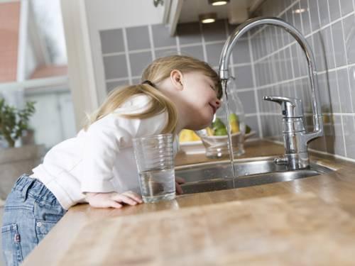 Ein kleines Mädchen in einer Küche trinkt Leitungswasser direkt aus dem Wasserhahn der Spüle