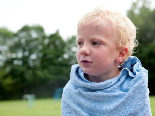 Ein blonder Junge ist in ein blaues Handtuch gewickelt. Im Hintergrund sind grüne Bäume und eine Wiese.