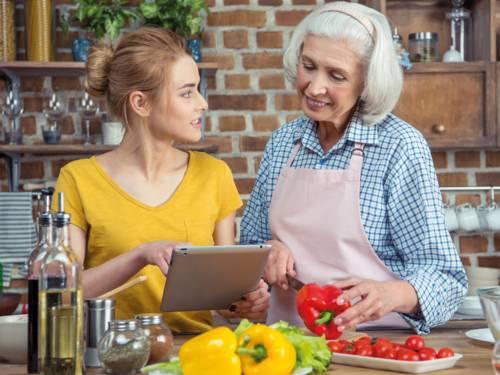 Junge und ältere Frau in einer Küche beim Kochen, die jüngere Frau hält ein Tablet in der Hand und zeigt der Älteren, die eine rote Paprika und ein Messer in den Händen hält, etwas auf diesem.