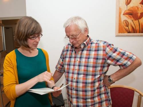Eine Frau und ein Mann stehen beieinander, sie zeigt ihm etwas auf einem Blatt Papier, das sie vor sich hält.