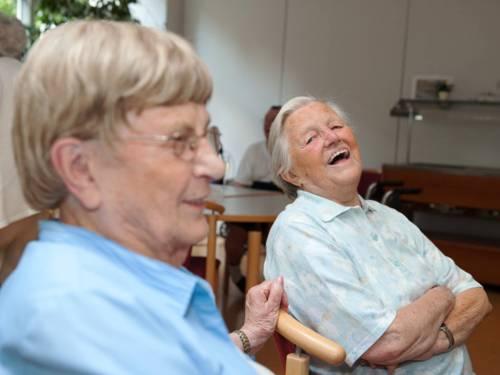 Zwei ältere Menschen sitzen nebeneinander auf Stühlen und lachen.