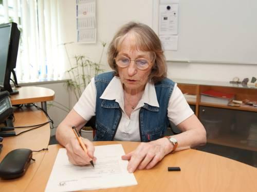 Eine ältere Frau sitzt an einem Tisch und füllt mit einem Stift ein Formular aus.