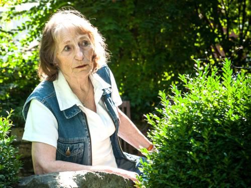 Eine Frau sitzt im Garten.