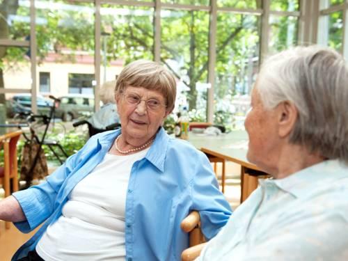 Zwei ältere Damen sitzen auf Stühlen und sprechen miteinander.