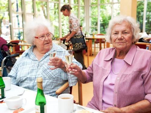 Zwei Seniorinnen stoßen mit einem Getränk an.