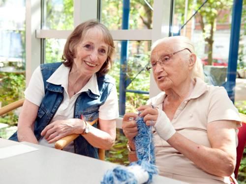 Zwei ältere Damen unterhalten sich, eine strickt währenddessen.