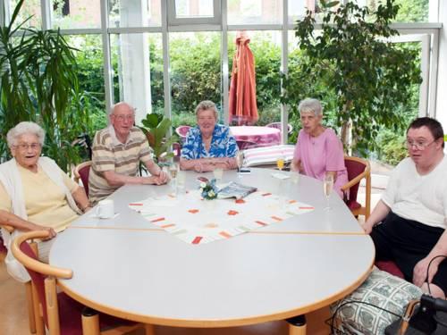 Fünf Bewohnerinnen und Bewohner einer Pflegeeinrichtung sitzen an einem großen Tisch eines Gemeinschaftsraums