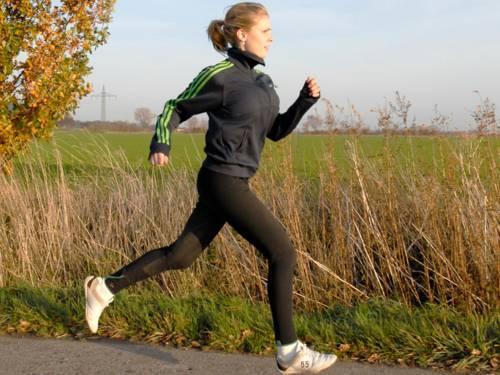 Eine Frau läuft auf einem geteerten Feldweg, kein Fuß berührt im Moment der Aufnahme den Boden.