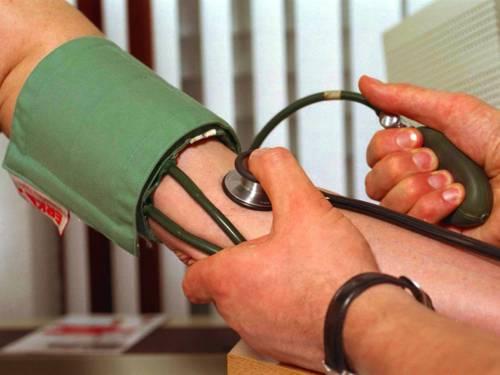 Die Manschette eines mechanischen Blutdruckmessgerätes (Sphygmomanometer) ist um den Oberarm eines Menschen gelegt. Eine zweite Person pumpt die Manschette mit einem Gummiball auf und ermittelt die Druckwerte mit dem Stethoskop.