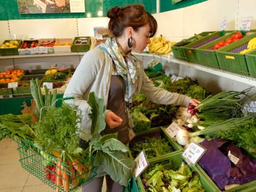 Eine junge Frau im Supermarkt. Sie ist gerade in der Obst- und Gemüseabteilung. In ihrem Einkaufskorb befindet sich bereits einiges an Gemüse (unter anderem ein Bund Karotten) und die Frau wählt weiteres Gemüse aus. In der linken Hand hat sie ein Bund rote Frühlingszwiebeln.