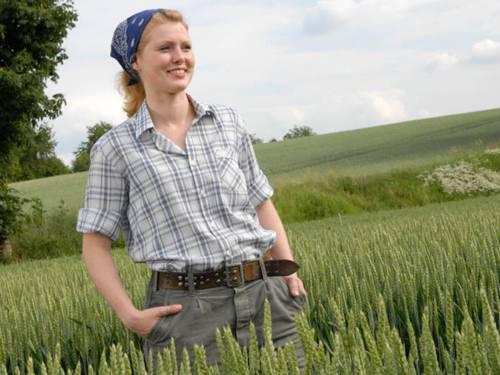 Junge, hemdsärmelige Frau, die in einem Getreidefeld steht, und über das Land blickt