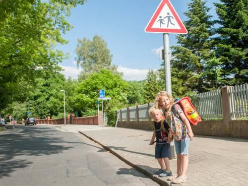 """Zwei Kinder stehen am Straßenrand vor dem Verkehrsschild """"Kinder"""" und schauen, ob die Straße, die sie offensichtlich queren wollen, frei ist"""