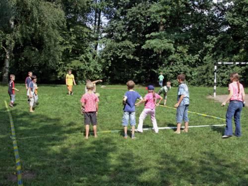 Auf einer Rasenfläche ist mit blau-gelbem Flatterband ein Spielfeld abgesteckt. Darauf spielen Kinder Völkerball: Die Kinder der gegnerischen Mannschaft werden mit einem Ball abgeworfen.