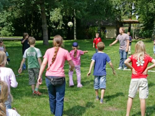Auf dem Bild sind zehn Kinder, eine Betreuerin und ein Betreuer abgebildet, die gemeinsam mit einem Ball spielen. Folienband auf dem Rasen markiert das Spielfeld.