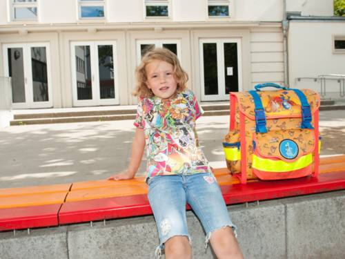 Mädchen mit Schulranzen auf der Bank vor einem älteren Gebäude sitzend