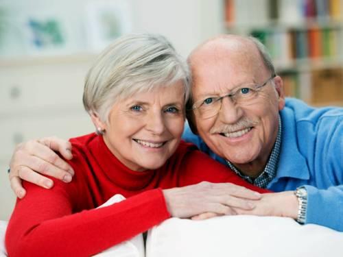 Zwei ältere Personen blicken in die Kamera, links eine Fraue, rechts ein Mann.
