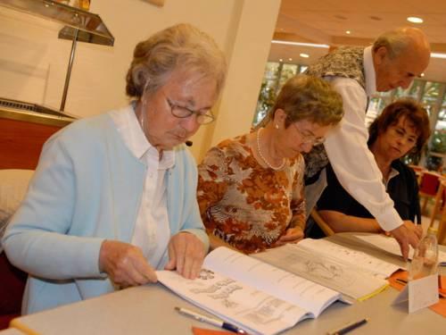 Drei Frauen sitzen und ein Mann steht an einem Tisch. Die beiden ältteren Frauen blättern in Unterlagen und der Männer zeigt der jüngeren Frau ezwas auf einem Blatt.