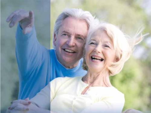 Ein älteres Ehepaar. Er zeigt auf etwas und beide sehen sehr glücklich aus.
