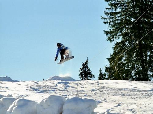 Nach dem Sprung über eine kleine Schanze fliegt ein Snowboarder über eine weiße Winterlandschaft. Der Himmel über ihm strahlt in hellem Blau.
