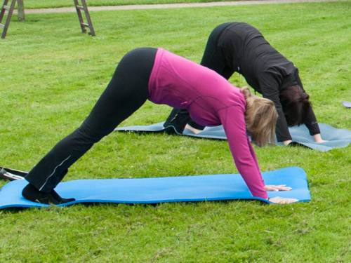Zwei Frauen auf einer Rasenfläche beim Yoga