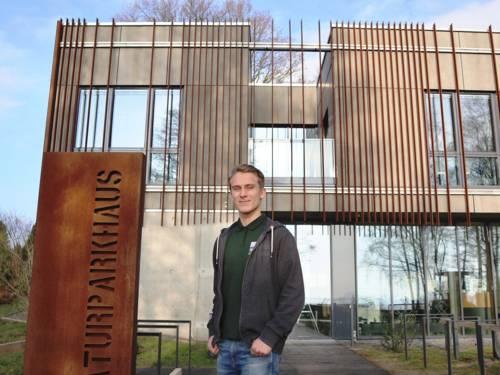 FÖJler Lukas Hahn steht vor dem Naturparkhaus in Mardorf.