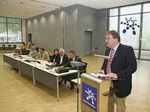 Der Regionspräsident an einem Rednerpult, das mit dem Regionslogo beklebt ist. Direkt neben ihm sitzen sechs weitere wichtige Verwaltungsmitarbeiter.