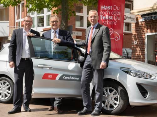 Drei Herren stehen an einem silbernen Auto.
