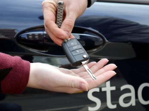Eine Hand übergibt einen Autoschlüssel in eine andere Hand.