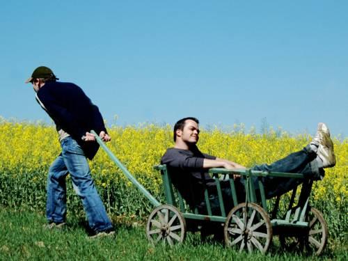 Ein junger Mann zieht einen Bollerwagen, in dem ein anderer junger Mann liegt, an einem Rapsfeld entlang.