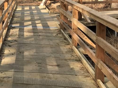 Holzsteg mit Geländer, Klopfleiste für Blindenstöcke, Aufmerksamkeitsfeldern