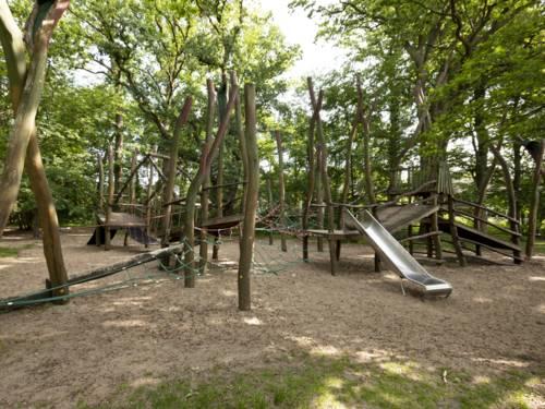 Abenteuerspielplatz mit Rutsche in mitten von Laubbäumen
