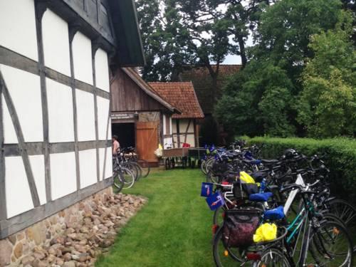 Auf einer kleinen Rasenfläche neben einem Fachwerkhaus sind nebeneinander viele Fahrräder aufgestellt.