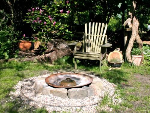 Ein Holzstuhl steht in einem Garten, im Hintergrund blüht Kirschlorbeer. Vor dem Stuhl steht eine Metallschale, die von Feld- und Kieselsteinen eingefasst ist.