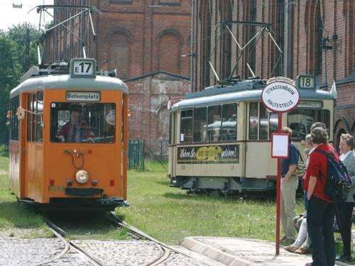 Zwei historische Straßenbahnen und Passanten an einer alten Straßenbahnhaltestelle