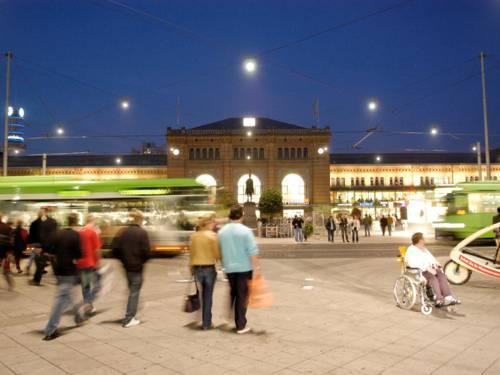 Menschen und Öffis vor dem Hauptbahnhof Hannover (bei Nacht).