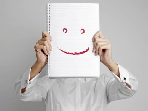 Ein Mann hält einen Schreibblock vor sein Gesicht. Auf dem Block sind zwei Augen und ein Mund gezeichnet.