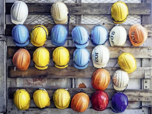 Viele bunte Bauarbeiterhelme.