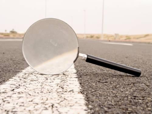 Eine Hand-Lupe steht hochkant auf einem weißen Fahrbahnstreifen.